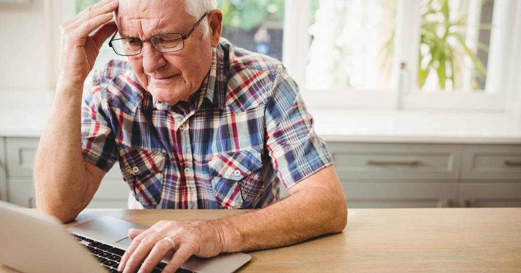 En äldre person använder laptop vid bordet. Hen ser tankfullt ut.