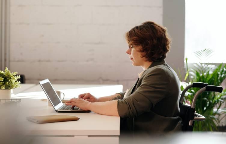 Nainen istuu tietokoneen äärellä.