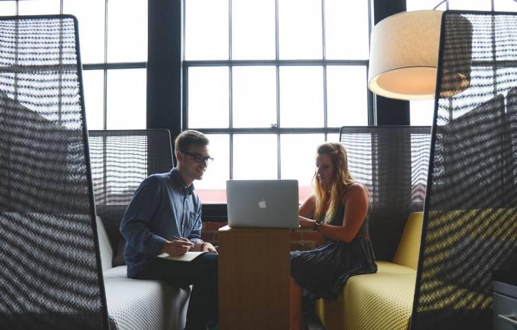 Mies ja nainen istuvat tietokoneen ääressä.